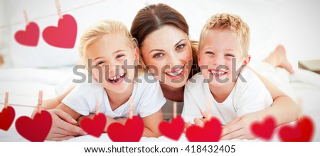 Laughing children playing with their mother lying on a bed against hearts hanging on a line - stock photo