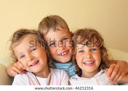 Laughing children three together in cozy room, two pretty girls and boy