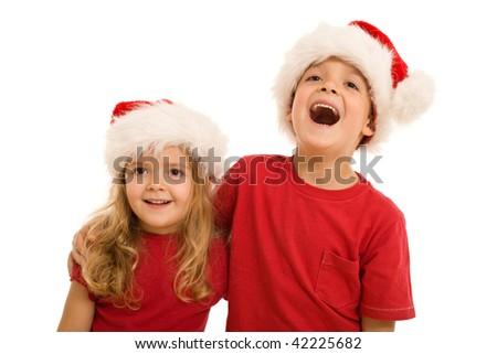 Laughing christmas kids looking aside, wearing santa hats - stock photo