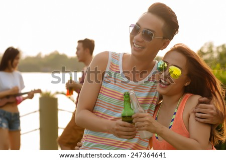 Laughing couple clinking bottles at the party - stock photo