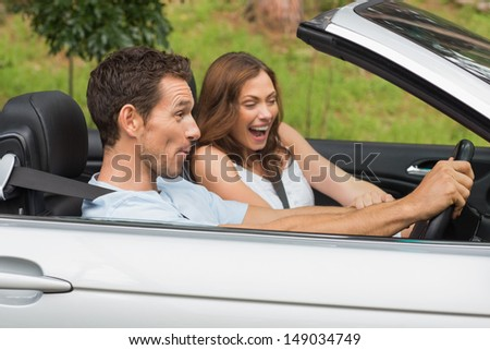 Laughing couple driving in a convertible in the countryside