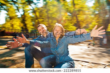 Laughing couple enjoy in riding On Roundabout. natural motion blur - stock photo