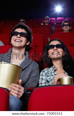 Laughing couple in 3D glasses in cinema - stock photo