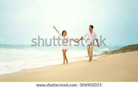 laughing couple in love holding hand enjoying in summertime - stock photo