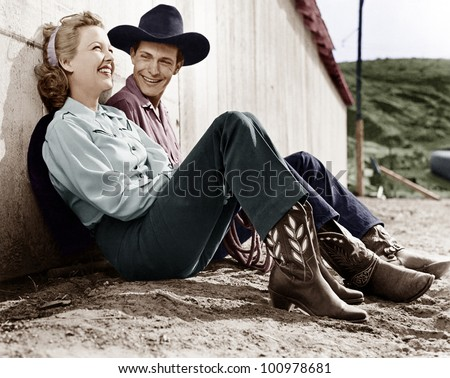 Laughing couple in western attire sitting on the ground - stock photo