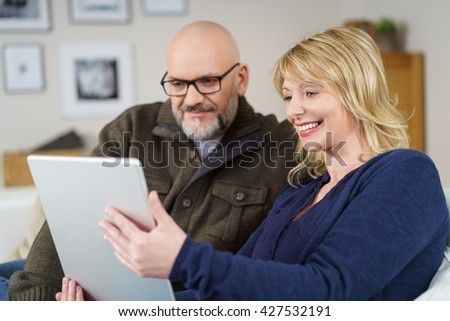 Laughing couple on couch reading their tablet while seated in the living room with framed photos on nearby wall - stock photo