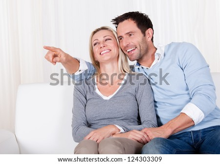 Laughing couple sitting close together on a couch pointing off screen to the left and looking in that direction - stock photo