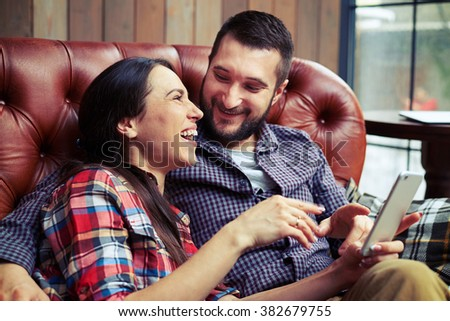 laughing couple sitting on sofa and using smartphone - stock photo
