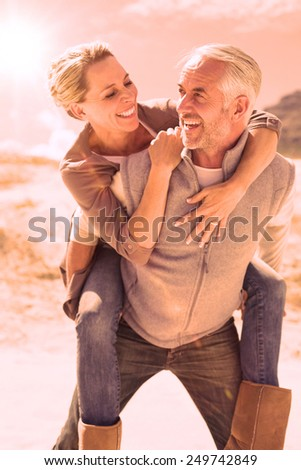 Laughing couple smiling at each other on the beach on a bright but cool day - stock photo