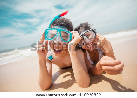 Laughing couple with goggles lying on the beach - stock photo