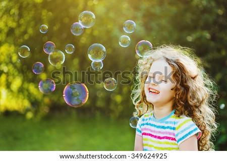 Laughing curly girl with bubbles.  Happy childhood concept. - stock photo