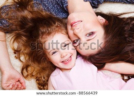 Laughing curly little girl and her mother - stock photo