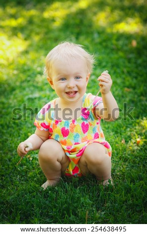 Laughing cute adorable blond baby toddler sitting on a meadow green grass during summer day holding flower dandelion - stock photo
