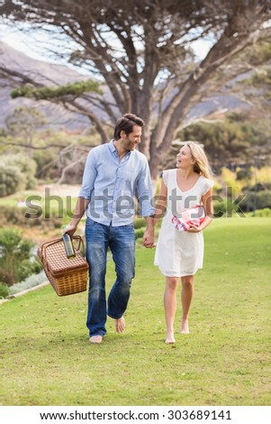 Laughing cute couple on date walking in the park - stock photo