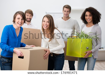 Laughing diverse multiethnic group of young friends moving house carrying cardboard boxes and houseplants in a teamwork concept - stock photo