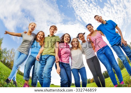 Laughing diversity friends stand on grass in row