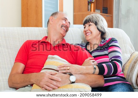 Laughing elderly couple relaxing on couch together