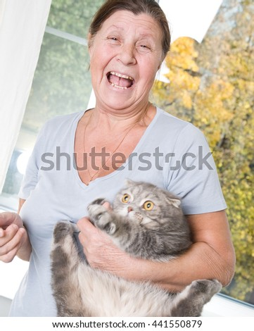 Laughing elderly woman trying to keep a restless cat. - stock photo