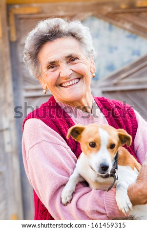 Laughing elderly woman with her kind little puppy outdoors. - stock photo