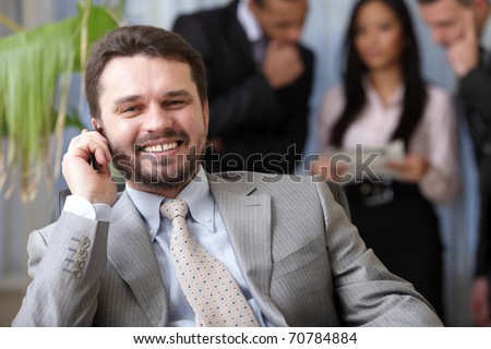Laughing executive businessman on the phone while his team is working behind