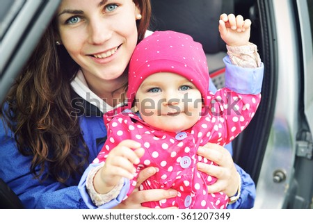 Laughing faces, mother holding adorable child baby girl, smiling and hugging. Mom and daughter outdoors in spring day. Beauty of smile, healthy kid, joyful, expressing love emotions. Close up border. - stock photo