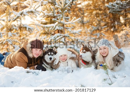 Laughing family and husky dog in winter park - stock photo