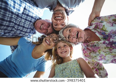 Laughing family forming huddle in back yard against sky - stock photo