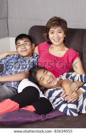 laughing family, mom daughter and son enjoy weekend together.