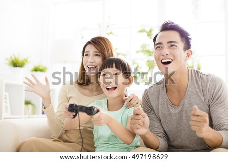 Laughing family playing video games in living room