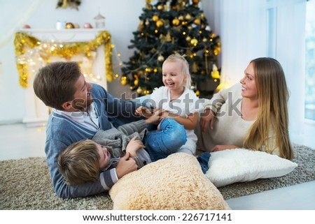 Laughing family with children at home - stock photo