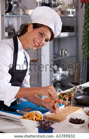 Laughing female chef preparing a small amuse on a stick - stock photo