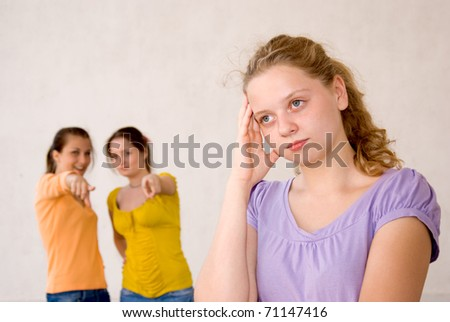 Laughing friends and sad girl over uniform background - stock photo