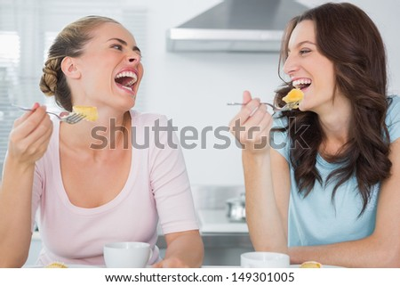 Laughing friends eating cake and having coffee in the kitchen - stock photo
