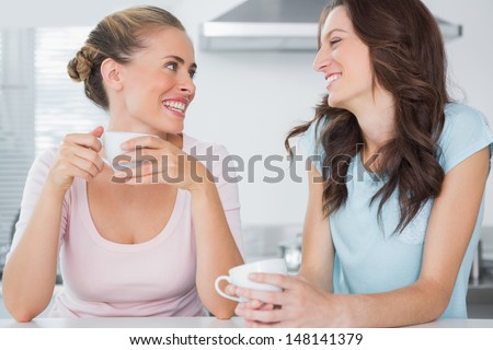 Laughing friends having cup of coffee in the kitchen - stock photo
