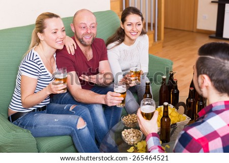 Laughing friends having fun at house party together - stock photo