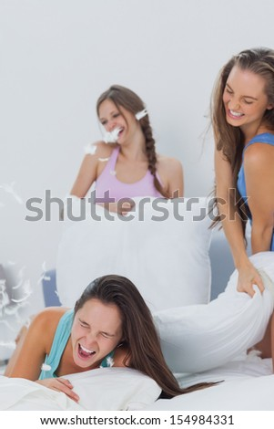 Laughing friends having pillow fight in bed at slumber party at home