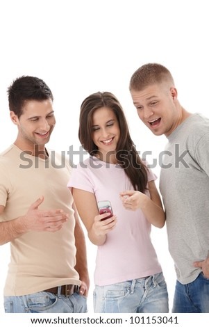 Laughing friends looking at mobile phone handheld by pretty girl pointing at phone, guy surprised. - stock photo