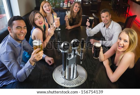 Laughing friends raising their glasses up looking at camera in the pub - stock photo