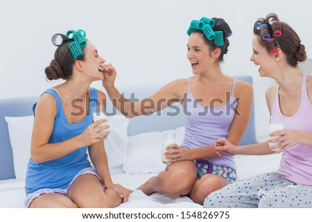 Laughing friends sitting in bed having milk and cookies at sleepover - stock photo