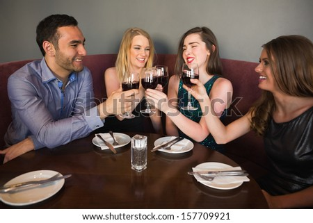 Laughing friends sitting together clinking glasses and chatting at a bar