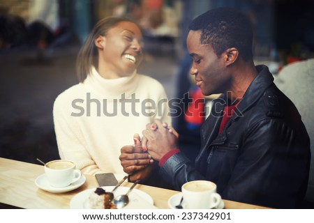 Laughing friends talk and drink coffee in cafe, good friend enjoying coffee in beautiful place, cold winter days in beautiful coffee shop, friends at breakfast having coffee and enjoying themselves - stock photo