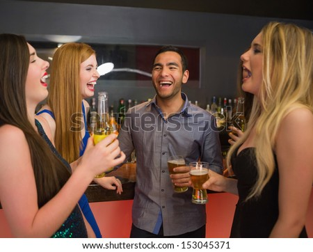 Laughing friends talking and drinking beer in the nightclub - stock photo