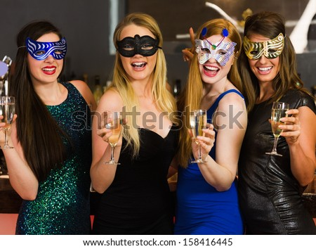 Laughing friends wearing masks holding champagne glasses looking at camera - stock photo