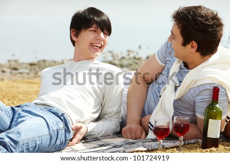 Laughing gay couple having a good time drinking red wine at beach - stock photo