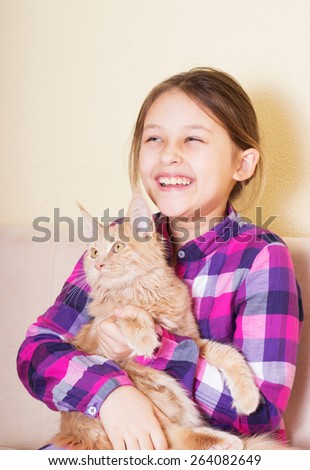 laughing girl and cat breed Maine Coon - stock photo
