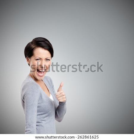 Laughing girl gives thumb up, isolated on grey - stock photo