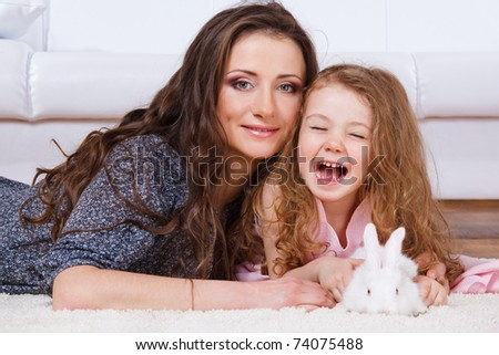Laughing girl, her mother and  a white bunny lying - stock photo