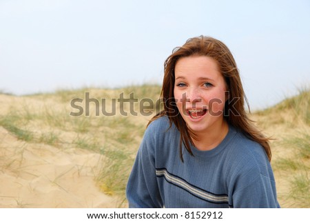 Laughing girl in sand dunes, looking at camera