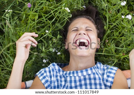 laughing girl lying on a lawn - rolling on the floor laughing - stock photo