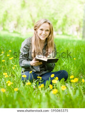 laughing girl sitting on grass with dandelions reading a book and looking at camera